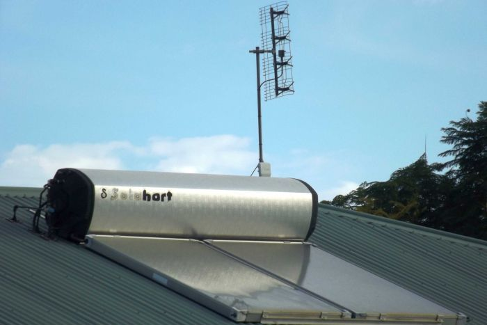 Rooftop solar hot water system on a roof under blue sky