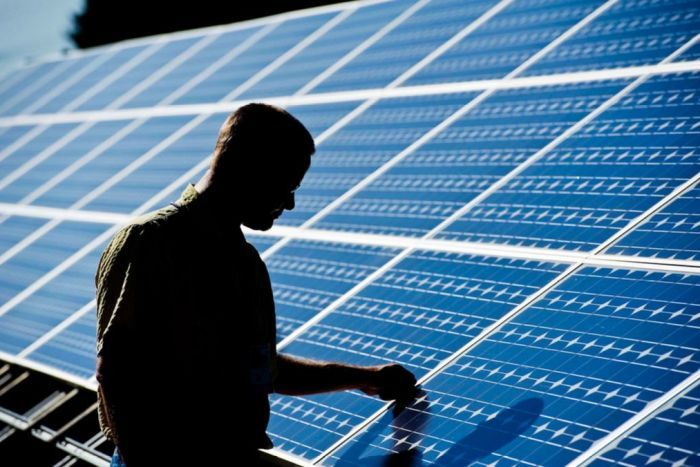 Silhouette of man checking solar panels
