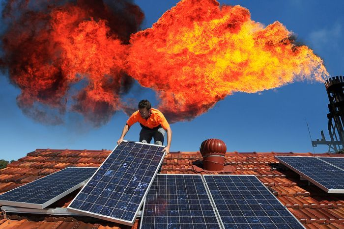 A worker installing rooftop solar panels with a industrial chimney venting a big flame behind.