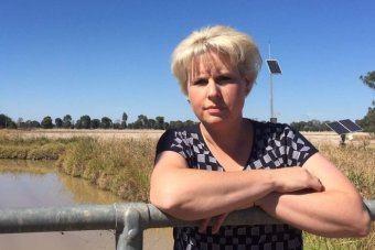 A woman with short blond hair leaning against a fence, with an irrigation channel in the background.