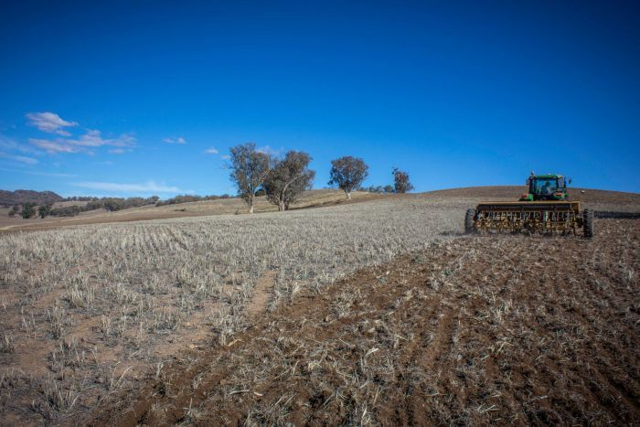 A tractor ploughing a dry paddock