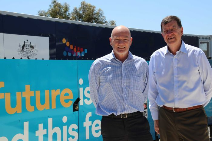 Greg Bourne and Andrew Stock stand in front of a large community battery at Alkimos Beach.