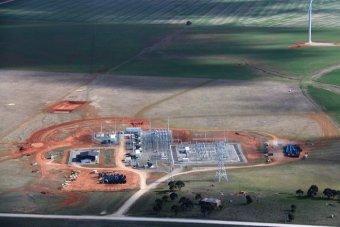 A electricity substation sits near turbines on a farm.