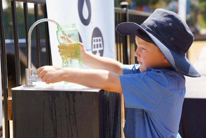 A primary school student fills water bottle from Source hydropanel tap.